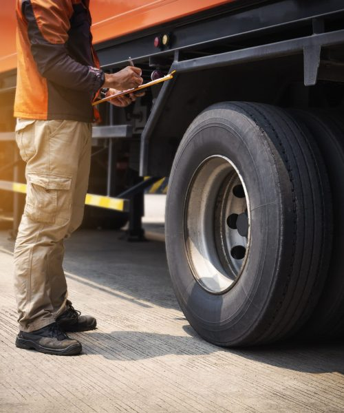 truck driver is inspecting safety tires truck.